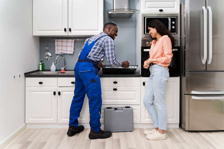 Photo pour Woman Looking At Serviceman In Uniform Fixing Induction Stove In The Kitchen - image libre de droit