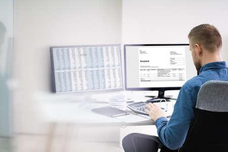 Foto de Close-up Of A Businessman Looking At Invoice On Computer At Workplace - Imagen libre de derechos
