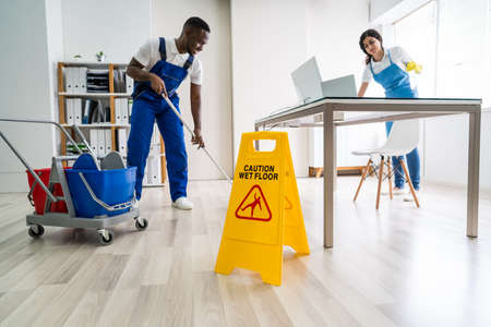 Photo pour Young Male And Female Cleaners Cleaning Office - image libre de droit