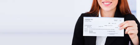 Photo pour Stimulus Check And PPP Loan Paycheck. Women Holding Payroll Cheque - image libre de droit
