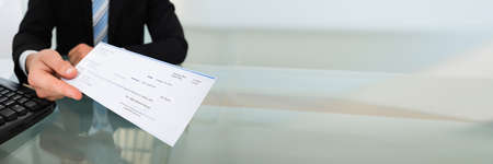 Photo pour Stimulus Check And PPP Loan Payment Cheque In Hand - image libre de droit