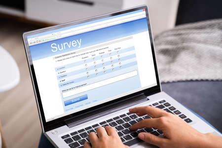 Photo pour Woman Looking At Online Survey Laptop Computer At Home - image libre de droit