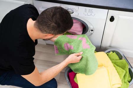 Foto de Man Doing Laundry. Stains On Clothes After Washing Machine - Imagen libre de derechos