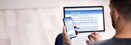 Photo pour Close-up Of A Man Filling Online Survey Form On Laptop And Smartphone - image libre de droit