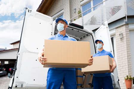 Foto de Furniture Move And Removal Using Truck Or Van With Face Mask - Imagen libre de derechos