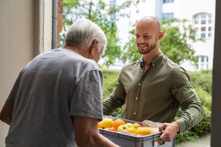 Photo pour Grocery Food Shopping Help For Elder Senior Standing At Door - image libre de droit