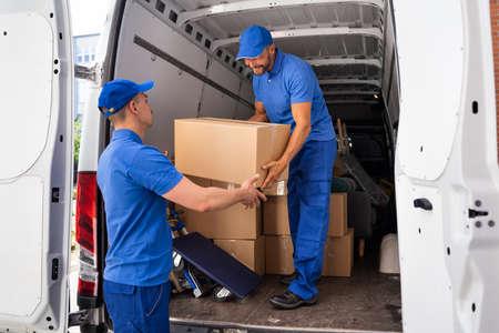 Foto de Home Moving Services. Movers Loading Van Or Truck - Imagen libre de derechos