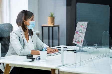 Foto de Employee In Office Social Distancing Using Sneeze Guard And Face Mask - Imagen libre de derechos