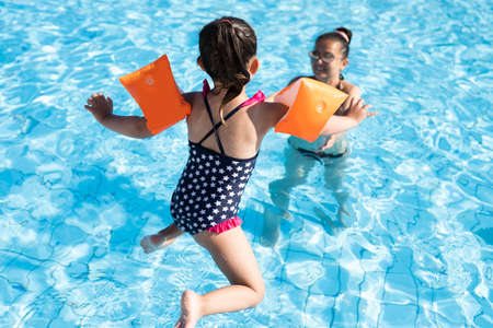 Photo pour Child Jumping In Swimming Pool In Summer - image libre de droit