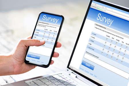 Photo pour Close-up Of A Businesswoman Hand Filling Online Survey On Mobile Phone - image libre de droit