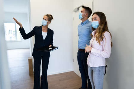Photo pour Happy Couple Buying New Home With Realtor Wearing Face Masks - image libre de droit