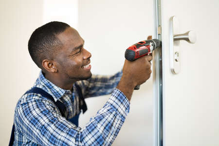 Photo pour African Locksmith Man Changing And Fixing Door Lock - image libre de droit