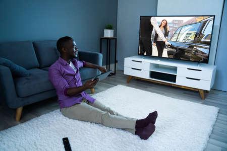 Foto de Large Version Of African Man Watching TV Movie Or Television - Imagen libre de derechos