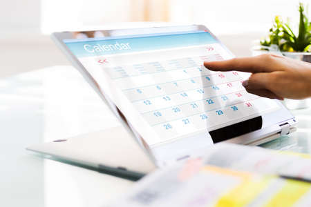 Photo pour Executive Looking At Calendar Agenda On Laptop Computer - image libre de droit