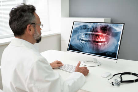 Photo pour Mature Male Dentist Looking At Teeth X-ray On Computer In Clinic - image libre de droit