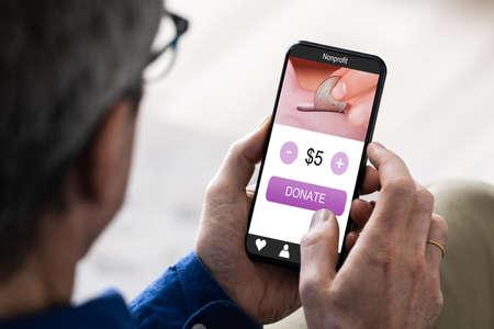 Photo pour Man Using Online Money Donation App On Phone - image libre de droit