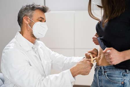 Photo pour Doctor Measuring Body Fat Using Fat Caliper In Clinic - image libre de droit