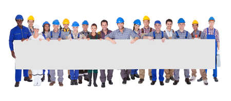 Photo pour Group Of Construction Workers Holding Placard Over White Background - image libre de droit