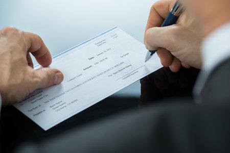 Photo pour Close-up Of Businessman Hand Filling Blank Cheque At Desk - image libre de droit
