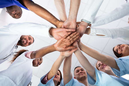 Photo for Low Angle View Of Doctor Stacking Hands Together In Hospital - Royalty Free Image