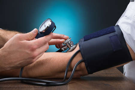 Photo pour Cropped image of male doctor checking blood pressure of patient at table - image libre de droit