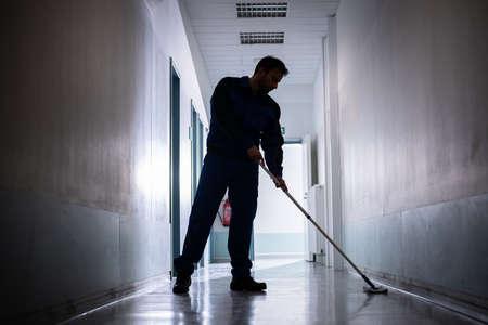 Foto de Professional Office Janitor Worker Cleaning Floor With Mop - Imagen libre de derechos