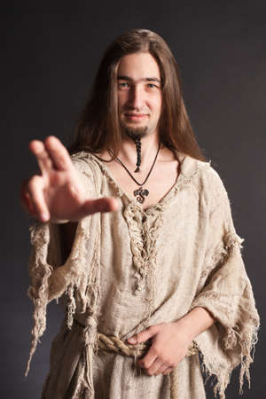 Handsome asian man with long hair makes a gesture blessing