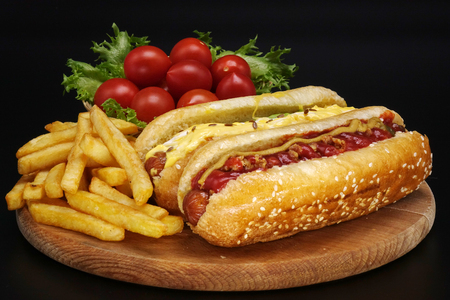 Photo for Hot dogs and French fries on black background. Sausages with tomato sauce and cherry tomatoes on a wooden Board. - Royalty Free Image