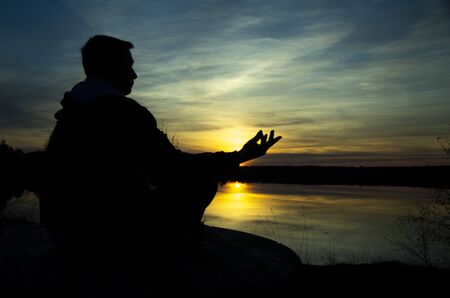 Photo pour Silhouette of a meditating man . The guy sits on a stone in the Lotus position and looks at the setting sun - image libre de droit