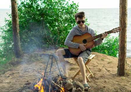 A teenager plays a guitar while sitting on the shore of a lake.の写真素材