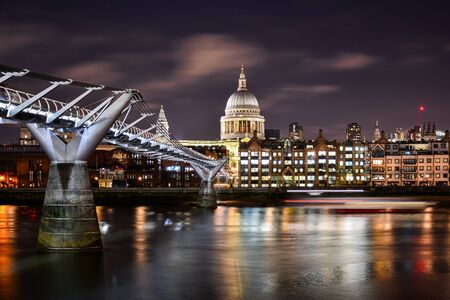 Photo for Beautiful night view of the illuminated dome of St Paul's Cathedral in the City of London, London, UK, with the River Thames and the modern Millennium Bridge - Royalty Free Image