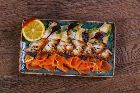 Sliced fish plate served lemon