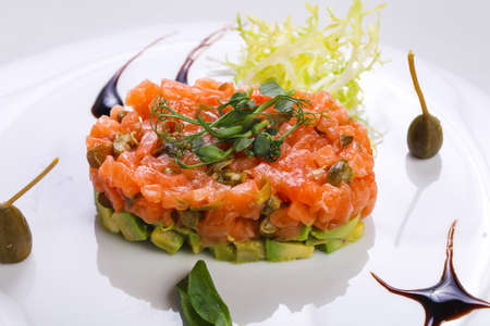Foto de Tartar with salmon and avocado served capers and balsamico - Imagen libre de derechos