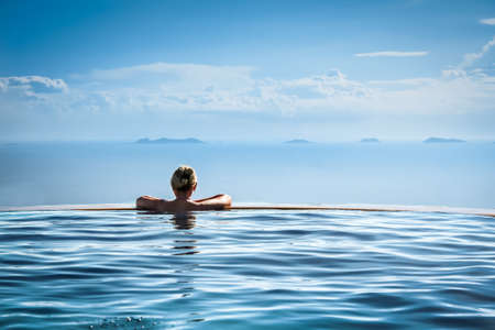 Woman relaxing in infinity swimming pool in luxury resort