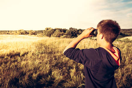 Young boy with binoculars in a wheat field looking into the distance. concept for future, discovery, exploring and education