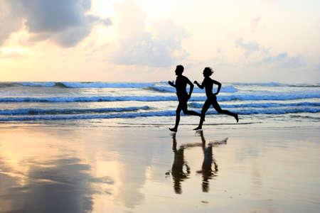 Photo pour Woman and men running during sunset  - image libre de droit