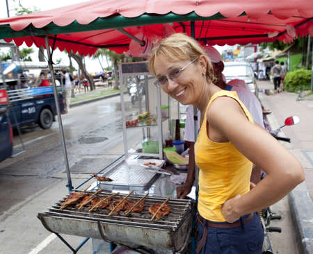 A woman buys traditional Thai food from street cooks