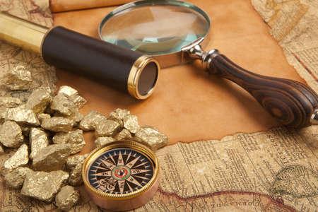 Photo pour Gold nuggets and vintage brass telescope on antique map - image libre de droit