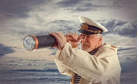 Photo pour Captain looks through a telescope - image libre de droit