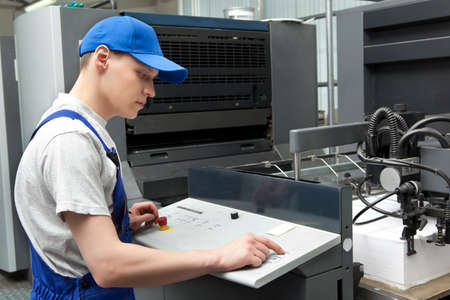 Young man in cap working in print factory
