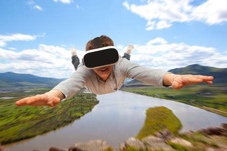 Photo pour Young man wearing virtual reality glasses flies over nature - image libre de droit