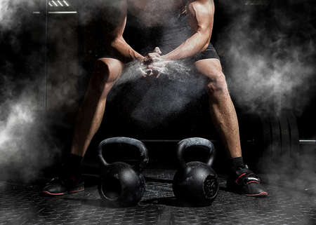 Foto de Weightlifter clapping hands and preparing for workout at a gym. Focus on dust - Imagen libre de derechos