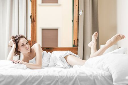 Photo pour Charming girl lies in bed. She stretched out her legs and looks playfully at the camera. The concept of relaxation, spa, hotels, personal care. Mixed media - image libre de droit