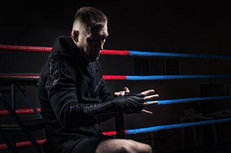 Photo pour Mixed martial artist wraps bandages around his fist. Concept of mma, ufc, thai boxing, classic boxing. Mixed media - image libre de droit