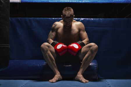 Foto de Boxer sits in gloves near the ring with his head bowed. The concept of sports, boxing, mixed martial arts, sports betting. Mixed media - Imagen libre de derechos