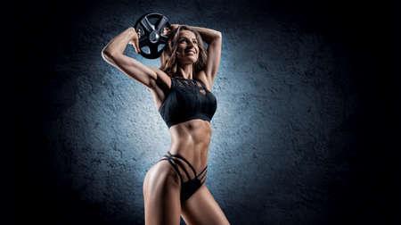 Foto für Delightful athlete posing in the studio with weights in her hands. The concept of sports, bodybuilding, sports nutrition. Mixed media - Lizenzfreies Bild