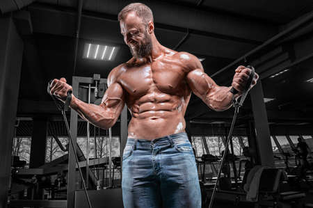 Photo for Professional athlete trains with elastic bands in the gym. Bodybuilding and fitness concept. Mixed media - Royalty Free Image