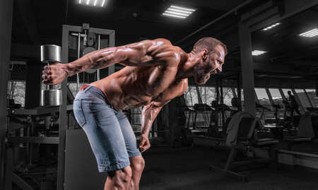 Photo for Professional athlete trains with a dumbbell in the gym. Triceps pumping. Bodybuilding and fitness concept. Mixed media - Royalty Free Image