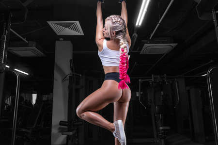 Photo pour Attractive busty girl pulls herself up on the bar. Fitness and bodybuilding concept. Mixed media - image libre de droit