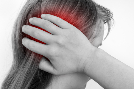 Woman with earache is holding her aching ear - black and white body pain concept